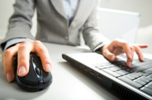 accountants for podiatrists - Close-up of female hand on mouse while working on laptop