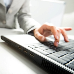 accountants for physiotherapists - Close-up of female hand on mouse while working on laptop