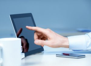 accountants for personal trainers - Hand pointing on modern digital tablet pc at the workplace.